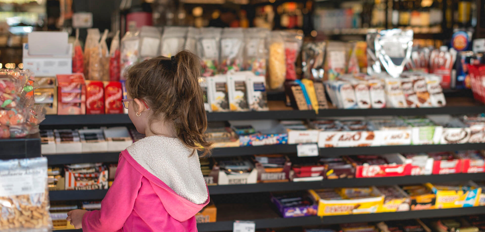 Little girl with pink sweather looking at a chocolate bar counter