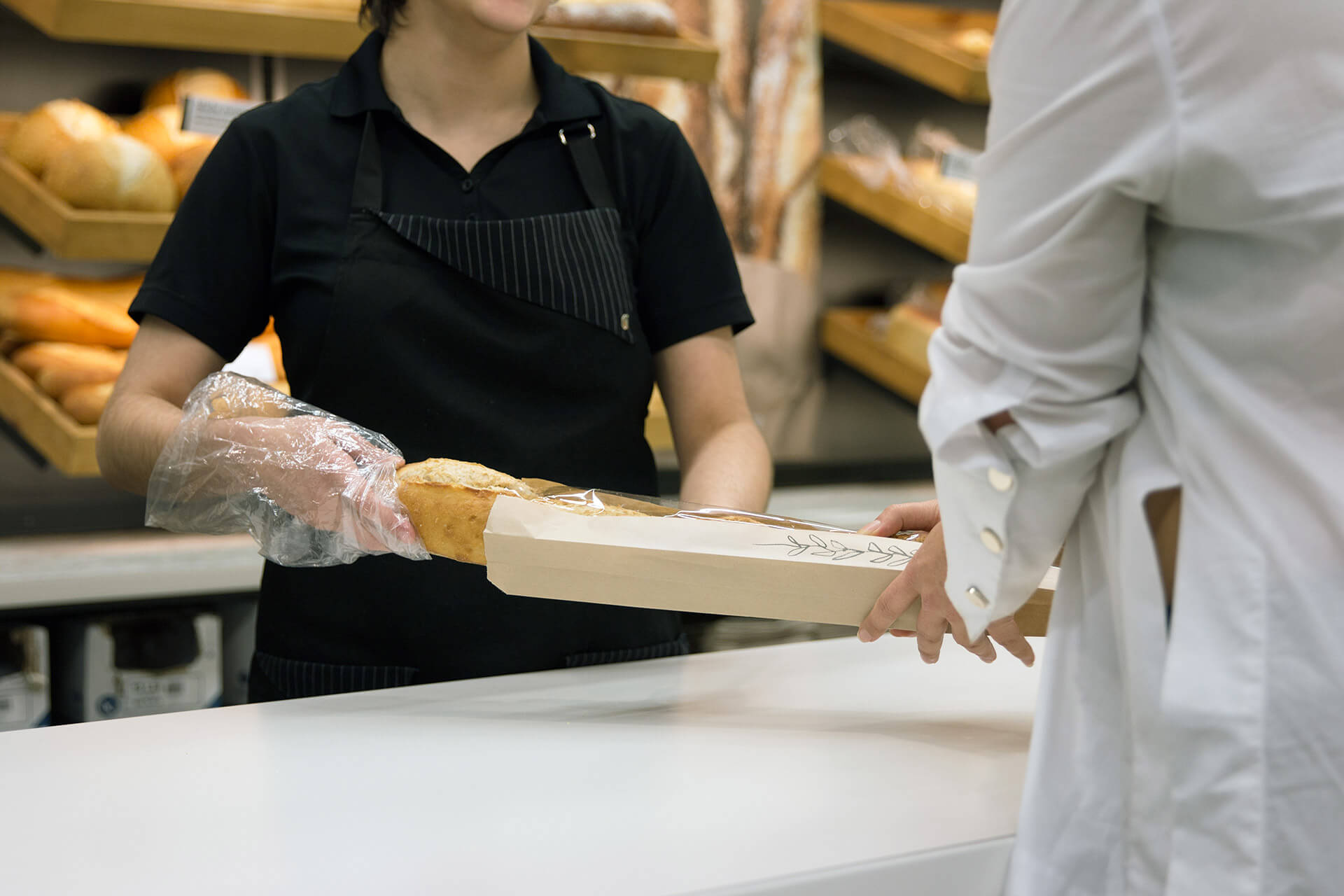 Baker giving a bread to a customer / Boulangère donnant un pain à un client